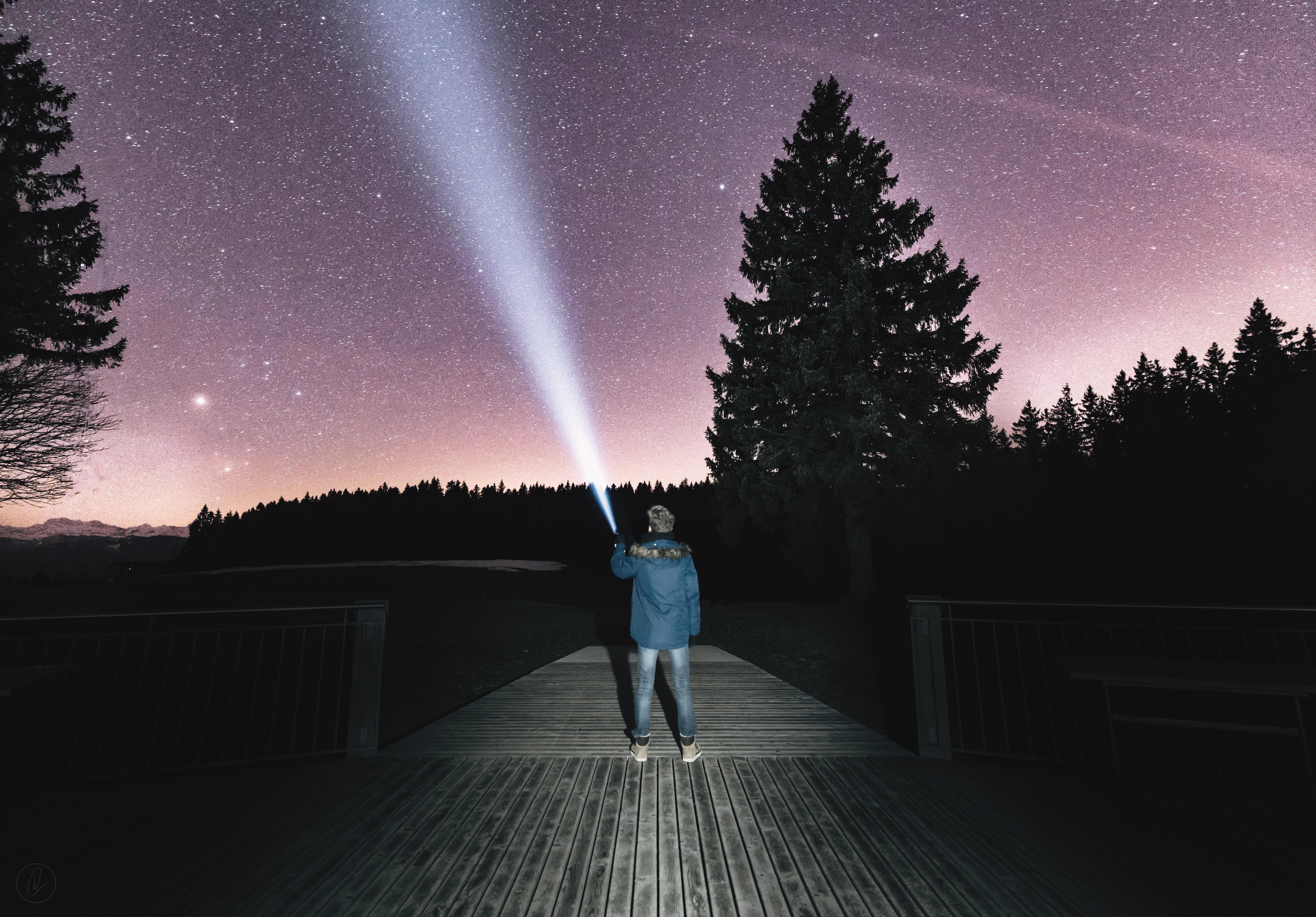 Man w:flashlight to sky